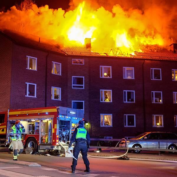 Husets tak som brinner. På gatan finns polis och brandkår.