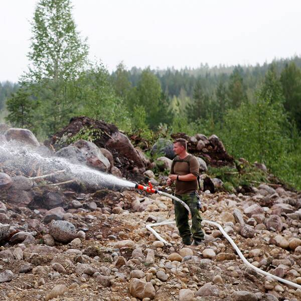 Brandman med vattenslang ute i skogen.