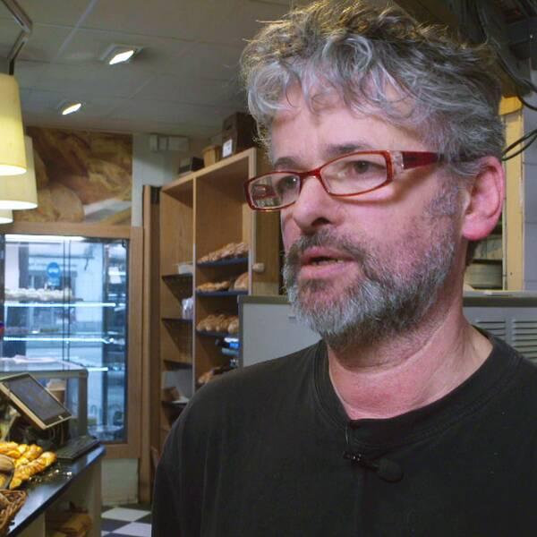 En man i ett bageri. Mannen har grått hår och röda glasögon. I bakgrunden syns bullar och bröd och ett skyltfönster ut mot gatan.