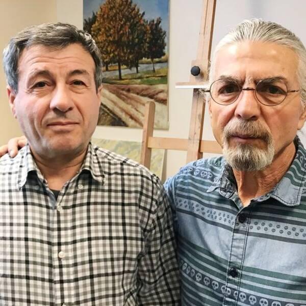 Aram Karabet och Talal Aboudan står i den senares ateljé. På väggarna hänger tavlor. De har rutiga skjortor på sig och Talal står med armen om Arams axel.