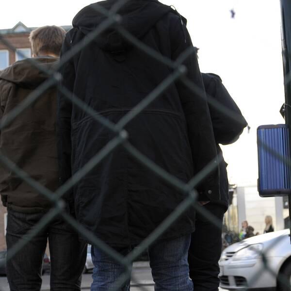 Ryggar av tonårskillar i jackor