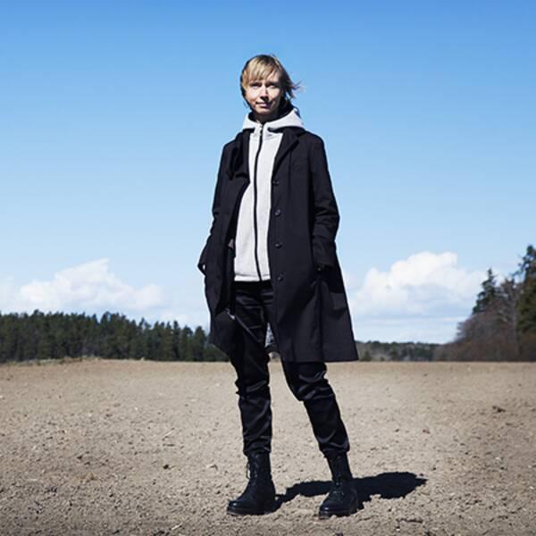 En stor blå himmel, en kvinna i svart jacka och svarta byxor på en åker.