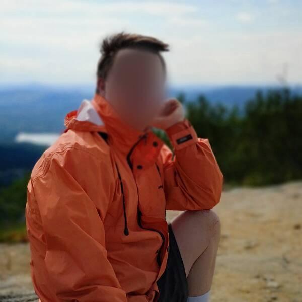 Man som sitter på en sten i naturen. Lutar huvudet i ena handen och har orange jacka.