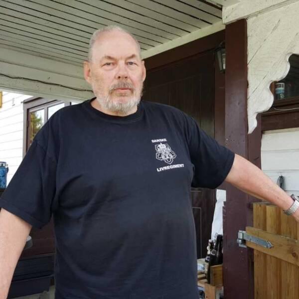 Man med vitt skägg i svart tshirt