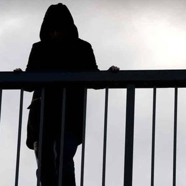 En mörk siluett står på en bro.