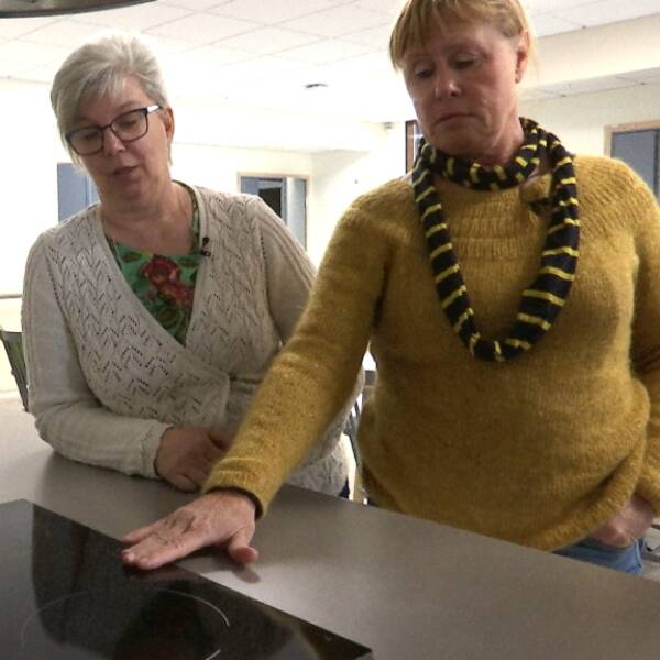 Kerstin och Bertha står och känner på spisen som är platt.