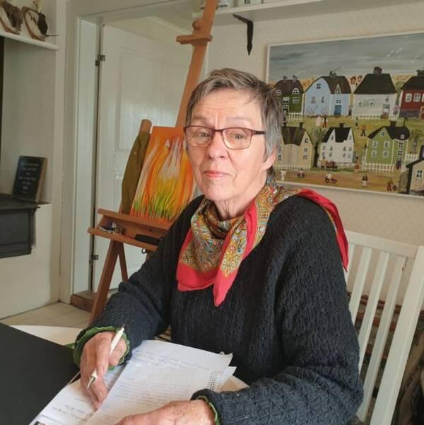 Wiwi Heggblad sitter i sitt kök med en pärm och papper framför sig. I bakgrunden en gammal vedspis och en tavla.