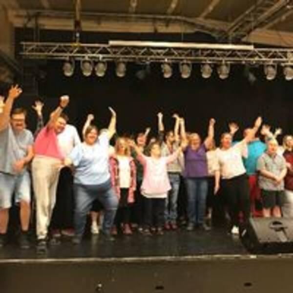 Glädje på stora scenen på Perrongen i Katrineholm. Flera personer höjer sina armar.