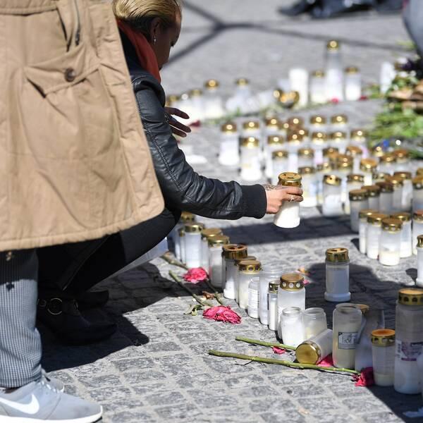En person tänder ljus vid en minnesplats för de tre personer som dödats i skjutningar i Sätra i Stockholm.