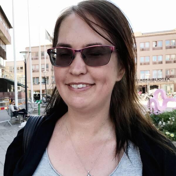 Sandra Johansson står på Olof Palmes torg i Örebro. Hon är iförd solglasögon, grått linne och svart kofta.