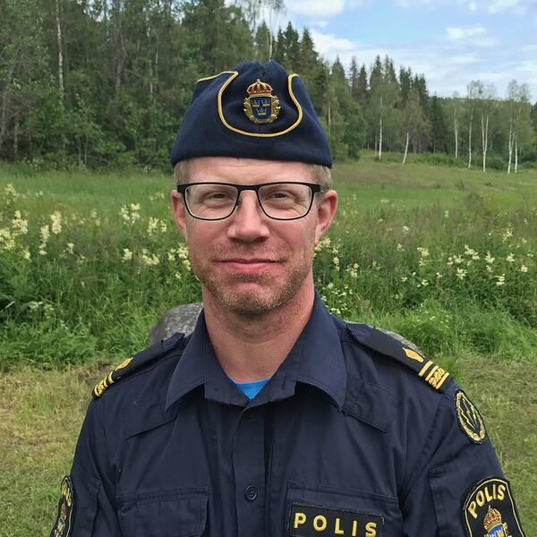 porträttbild på en man i polisuniform framför en äng med skog i bakgrunden