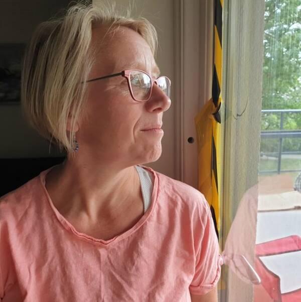 Annika står vid balkongdörrens fönster, nära den gulsvarta tejpen. I bakgrunden ser man en lastpall och gröna löv på trädet en bit bort.
