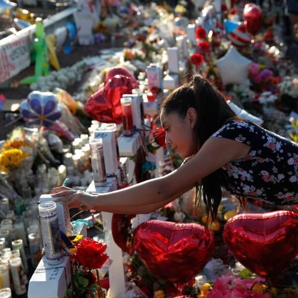 Människor sörjer vid minnesplats för dådet i Texas. Platsen är full av blommor, ljus och ballonger.