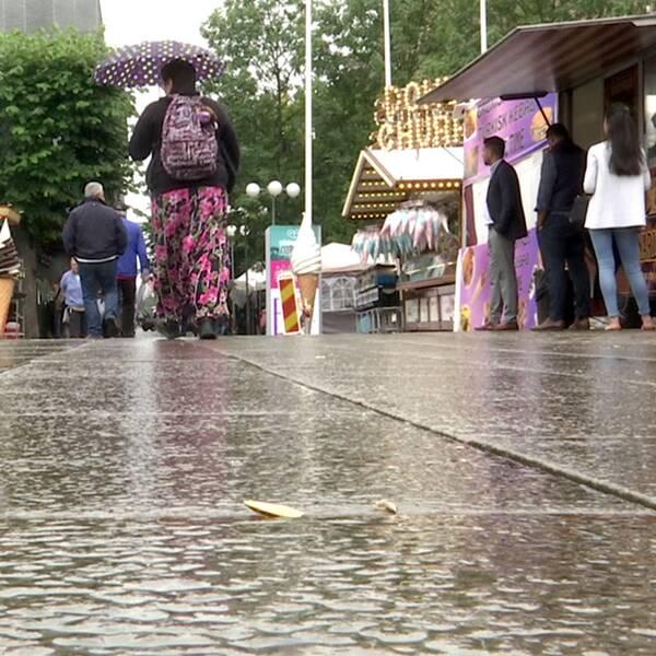 Besökare på Södertäljefestivalen i regn och i mitten promenerar en dam med paraplymellan matstånden.