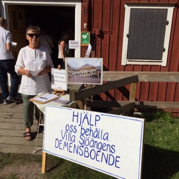 """Wiwi står med solglasögon bredvid en skylt: """"Hjälp oss behålla Villa Sjöängens demensboende"""""""
