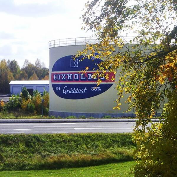 vy över väg och träd mot rund byggnad med varumärkesskylt för Boxholms gräddost