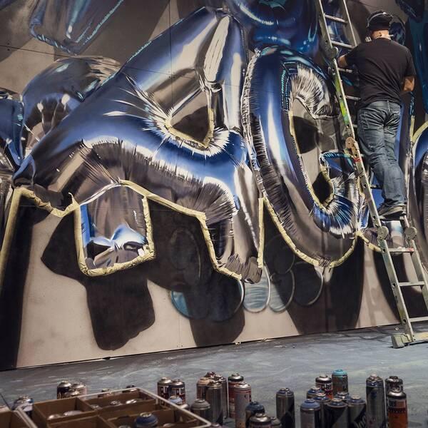 """Konstnären Huge färdigställer sitt verk inför öppningen av street art-utställningen """"Magic City"""" på Magasin 9 i Frihamnen, 2017."""