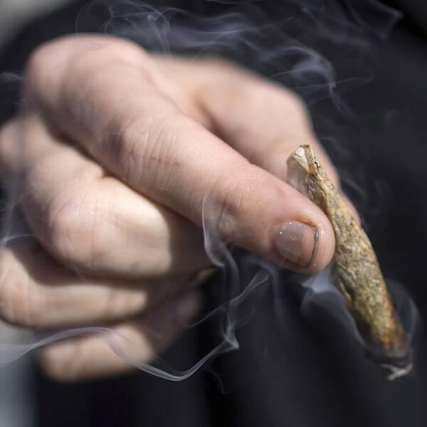 En person som röker cannabis och en skylt som säger att cannbis säljs.