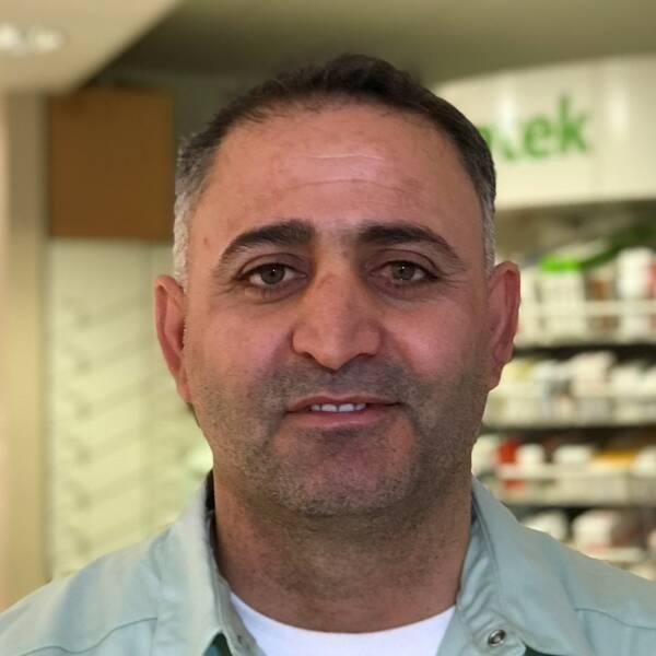 Ali Darwish framför hyllor med mediciner