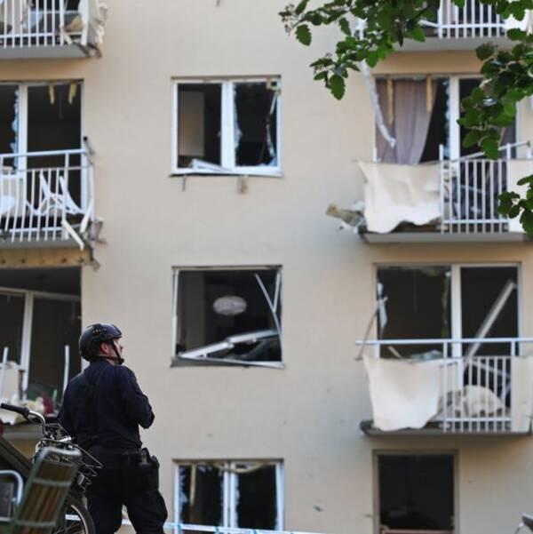 Skadade balkonger på en husfasad efter explosionen i Linköping. En polis med hjälm tittar upp mot fasaden.