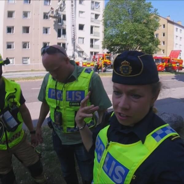En hjälm i förgrunden. Polisen Angelica Axelsson gestikulerar med armarna. Bakom henne står en brandman och en polis.