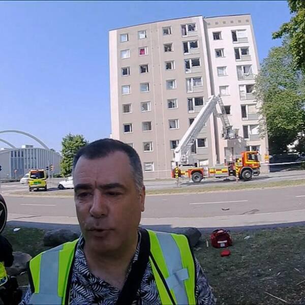 Magnus Skoglund står på explosionsplatsen i gul reflexväst. I bakgrunden ser man ett hyreshus med krossade fönster och räddningstjänstens stegbil.