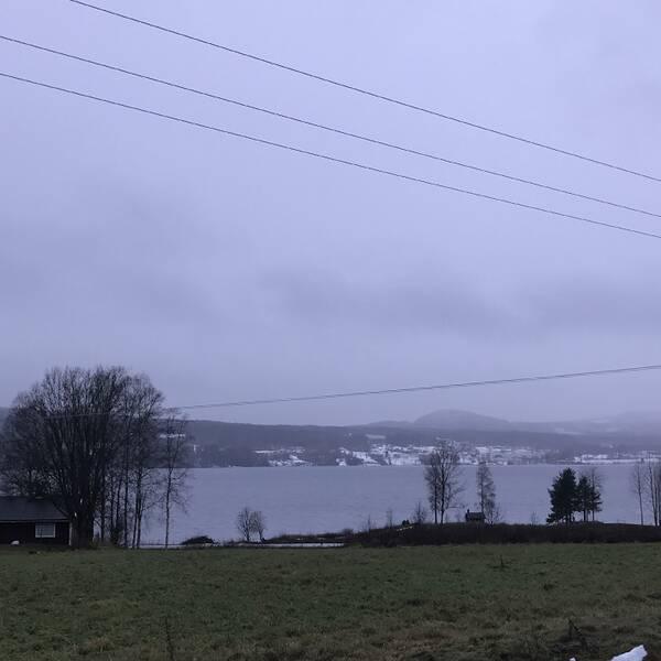 Fryken, Lysvik Värmland den 9/12 vid lunchtid.Ängen lyser grön på östra sidan medan snön ligger kvar på västra sidan av Fryken.Duggregnet har övergått i regelrätt regn/snöblask i +2grader