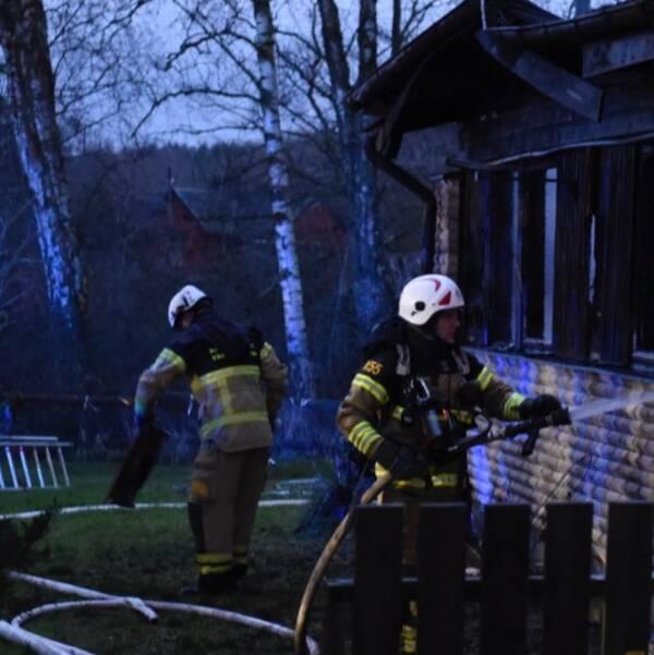 Två brandmän som läcker villabrand. Lågor syns inifrån huset.