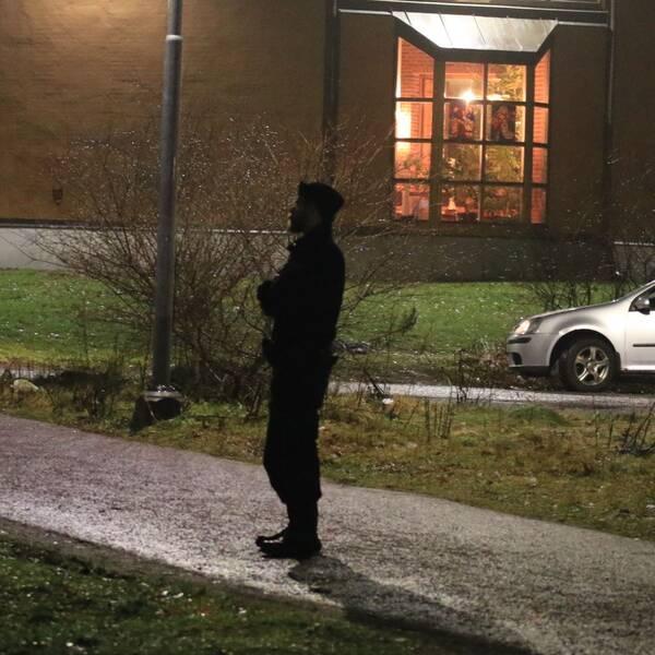 Polis står på brottsplats, bil och hus syns också i bild.