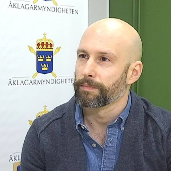 Bild på skallig man med skägg framför en roll-up som det står Åklagarmyndigheten på