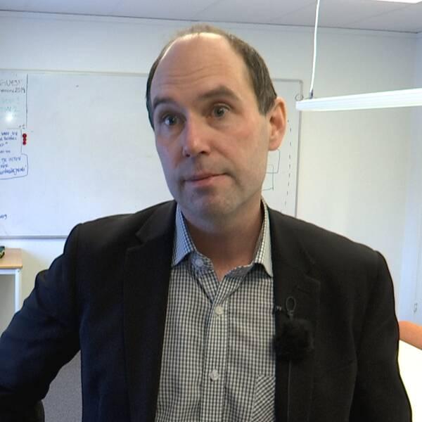 En man i ett litet konferensrum iförd kavaj och skjorta