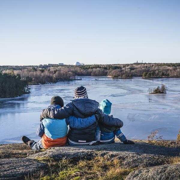 Tre personer sitter på klippa med utsikt över sjö.
