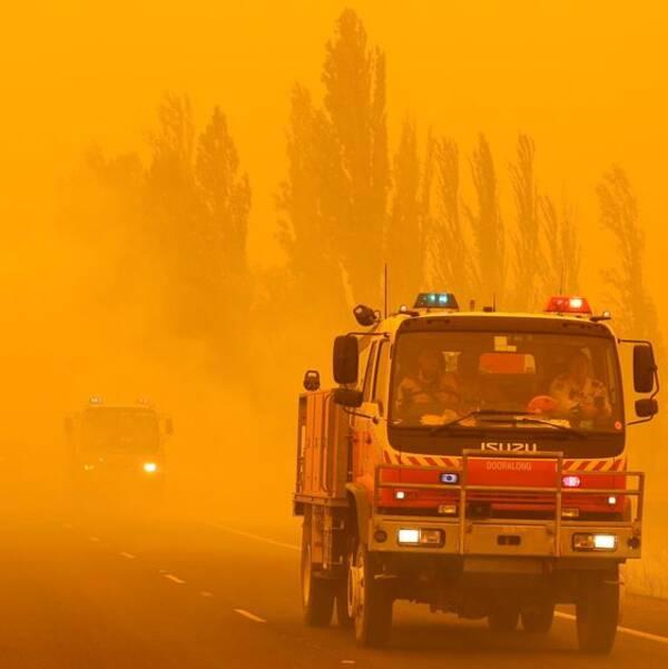 En brandbil kör genom rödgul rök i Australien