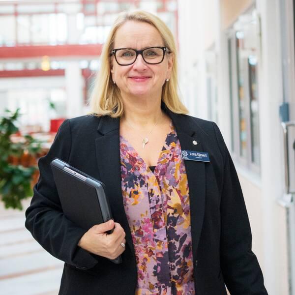 """Delad bild: Lena Gjevert och skylt med texten """"regionens hus – Region Värmland""""."""