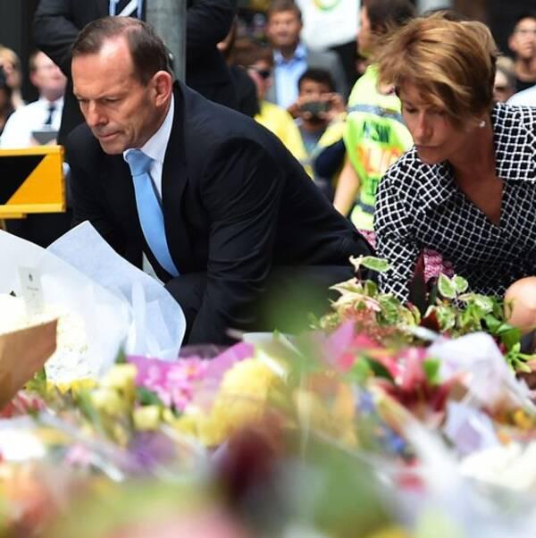Premiärminister Tony Abbott (L) och hans fru Margaret lägger ner blommor nära den plats där det blodiga gisslandramat fick sitt slut.