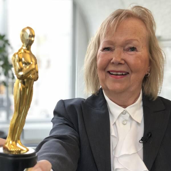 Anneli Ahlbom håller fram en Oscarsstatyett.