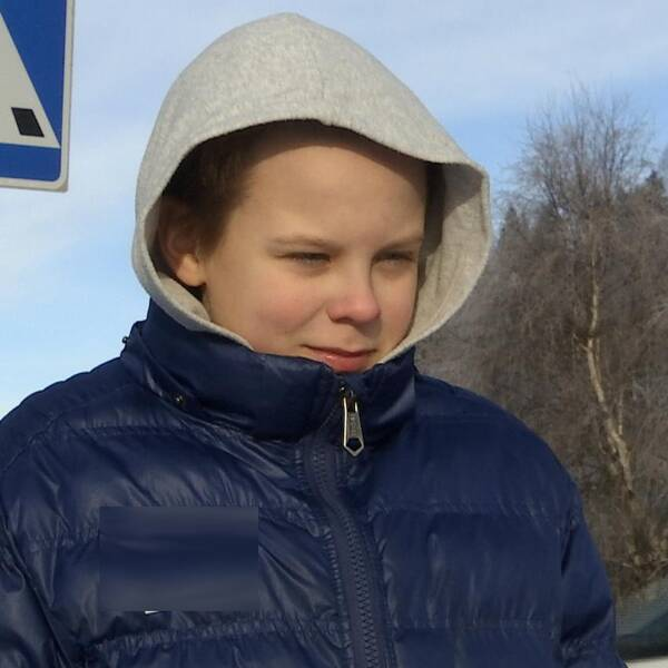 Yngre pojke i blå jacka och grå huva.