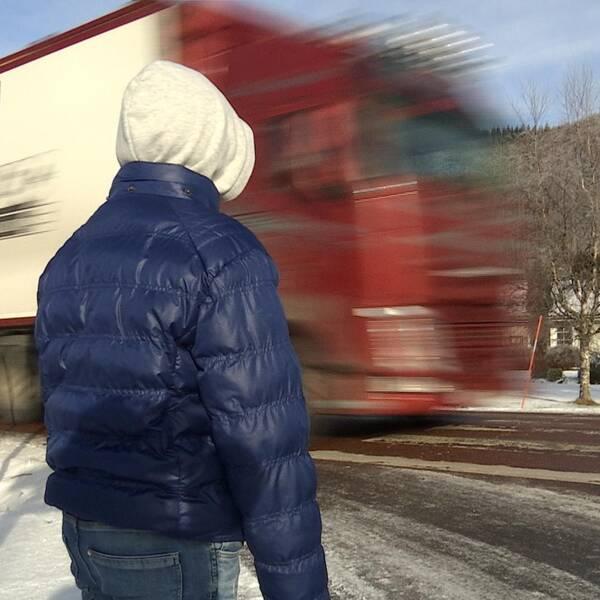 Barn i blå jacka står vid ett övergångsställe där en lastbil precis kör förbi.