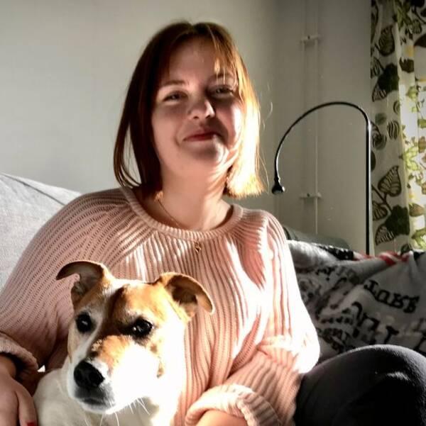 Amanda Wall i rosa tröja sitter i en grå soffa med en liten brunvit hund.