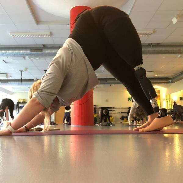 Kvinna står i yogaposition, hennes ena ben är en protes.