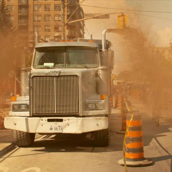 En parkerad lastbil som spyr ut avgaser på förbipasserande cyklist.