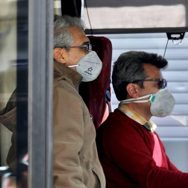 Människor med ansiktsmask åker buss i Teheran.