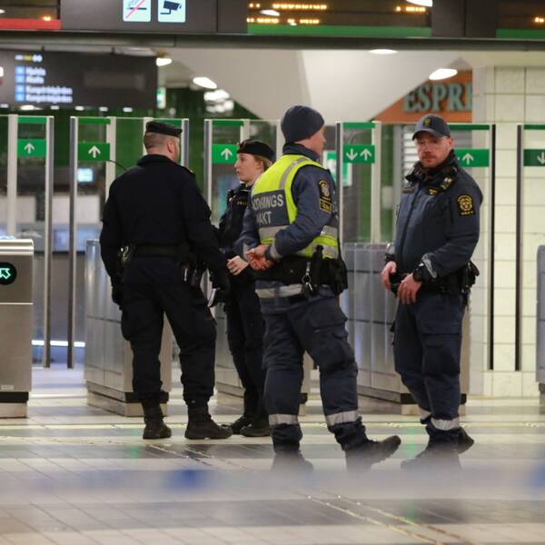 Poliser står innanför avspärrningsband