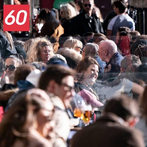 Människor på fullsmockad uteservering i solsken.