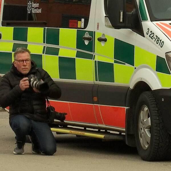 Fotografen Öyvind Lund står på knä bredvid en sjuktransportbil och fotograferar.