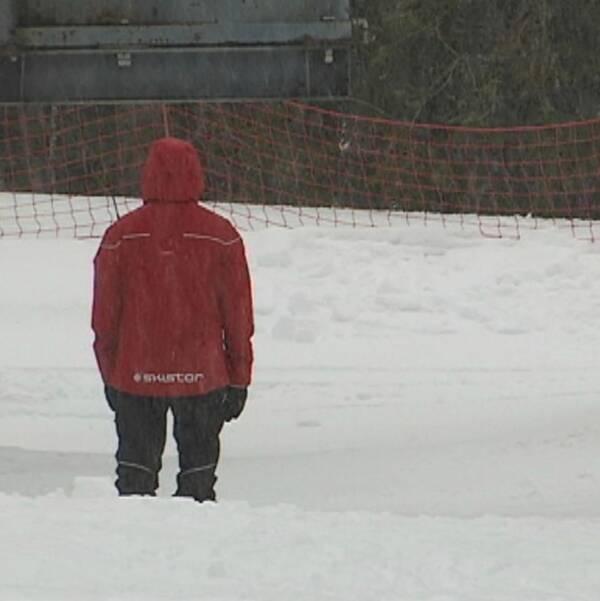 Man i mössa och vinterkläder står ute i snöfall. Bild ensam liftskötare i röd jacka med texten Skistar.