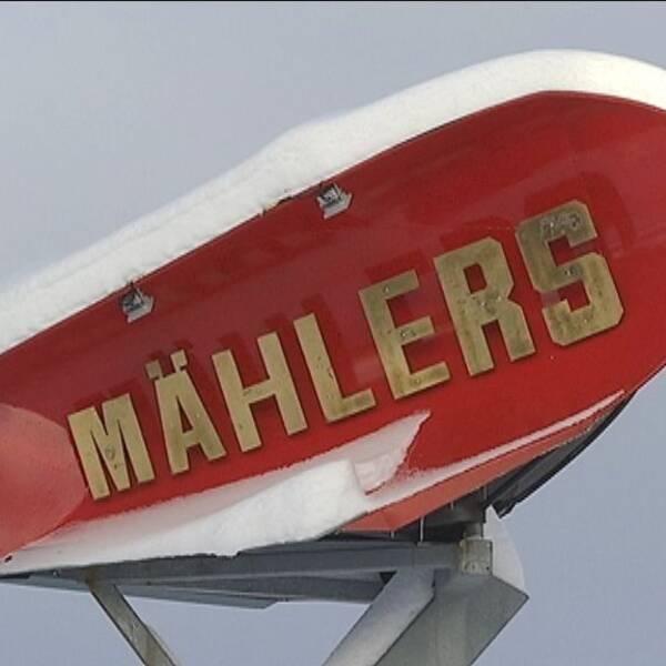 Röd snöplog på en pelare med texten Mählers i guld.