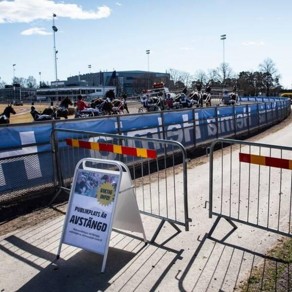 I förgrunden en skylt som visar att publikplatserna är avstängda, och i bakgrunden kör ekipagen i ett travlopp förbi på Färjestadstravet i Karlstad.