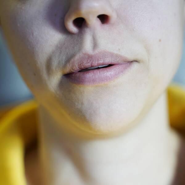 Närbild på en kvinnas mun under utandning.