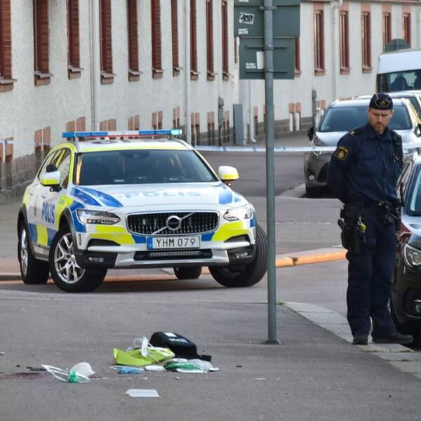 polisbilar och bilar vid trottoar, polisman står och tittar på saker som ligger på marken